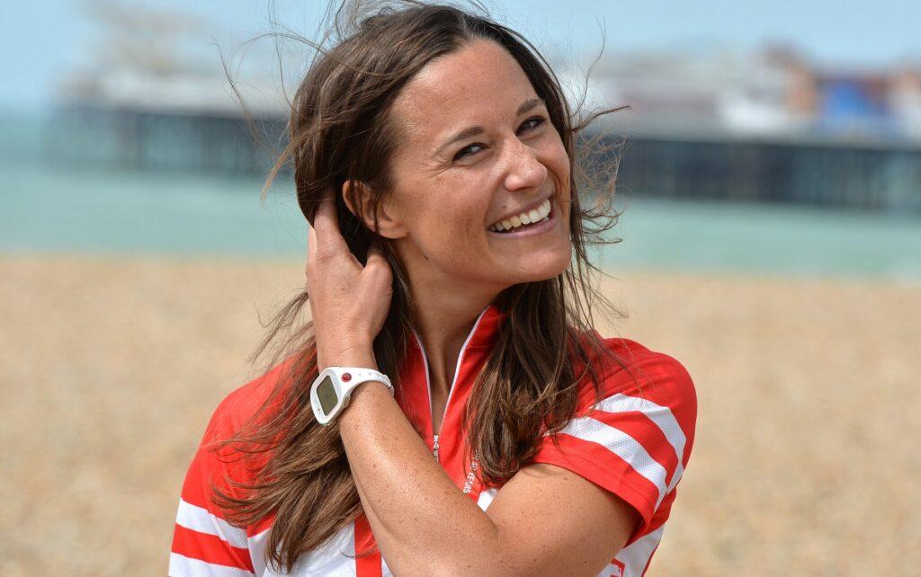 Pippa Middleton pe plajă îmbrăcată într-un tricou roșu cu dungi albe, în timp ce își ține părul și zâmbește la cameră după ce a terminat un tur caritabil cu bicicletele în Londra în 21 iunie 2015 pentru fundația British Heart