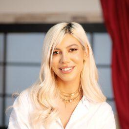 Portretul artistei Sore îmbrăcată într-o cămașă albă în timp ce zâmbește la camere