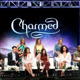 actorii principali ai serialului fantasy Charmed așezați pe scaune și îmbrăcați în ținute elegante în timp ce în spate se află un panou albastru cu titlul serialului Charmed la priemiera care a avut loc în 2018