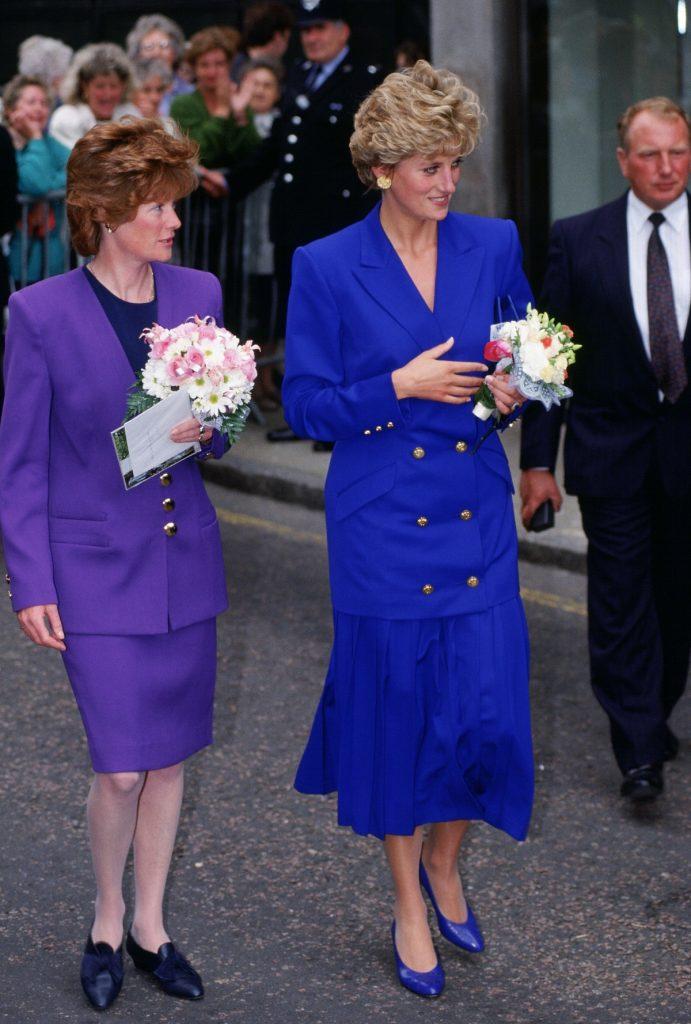 Prințesa Diana îmbrăcată într-o fustă albastră și un sacou lung de aceași culoare alături de sora sa Lady Sarah McCorquodale într-o vizită oficială de la Nottingham din 1992