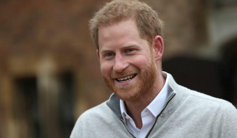 Ducele de Sussex zâmbește larg, în timp ce este îmbrăcat într-o cămașă și un pulover de culoare deschisă