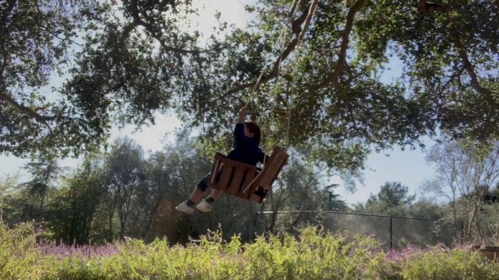Micuțul Archie în timp ce se dă în leagăn într-o grădină plină de verdeață și se bucură alături de familie