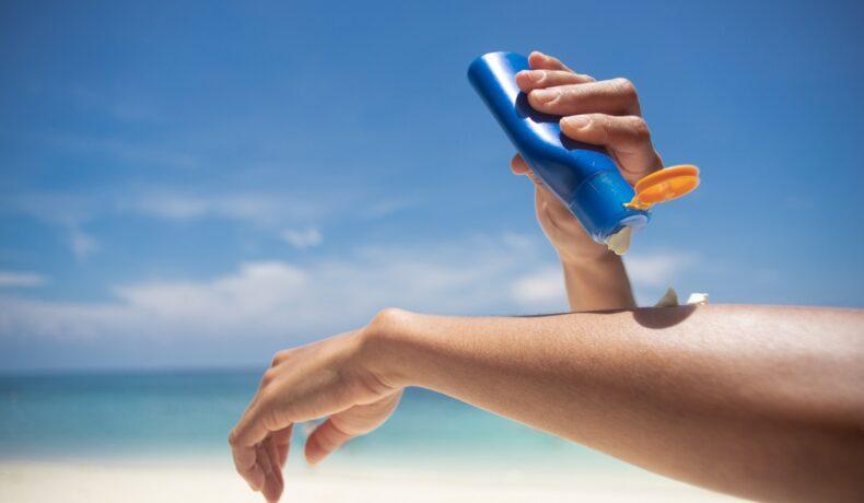 O femeie care își aplică pe brațe produse cu protecție solară în timp ce se află pe o plajă