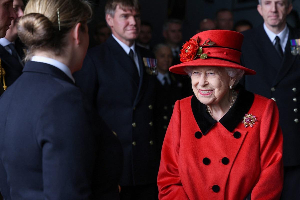 Regina Elisabeta într-un costum roșu la vizita portavionului HMS Regina Elisabeta în timp ce se salută cu oficialitățile de la bord și poartă în piept broșa primită de la Printul Philip cadou în 1966