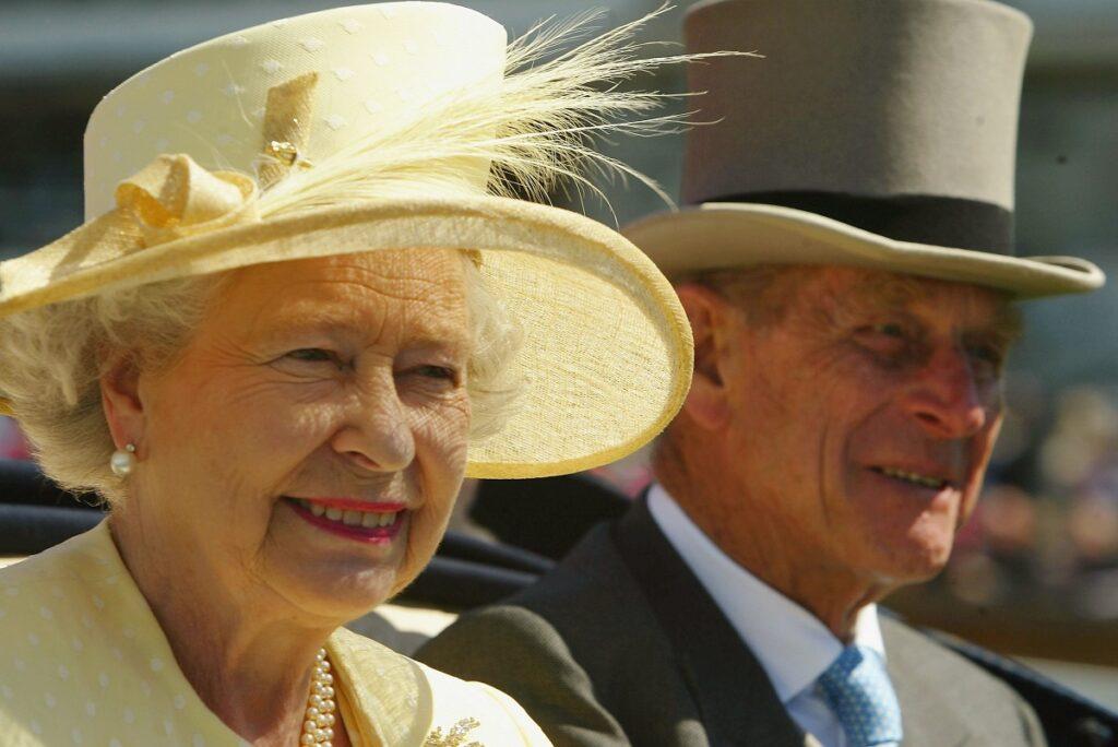 Portret cu Regina Elisabeta purtând o bluză și o pălărie cu pană galbene, alături de amintirea Prințului Philip îmbrăcat la costum și purtând o pălărie înaltă gri