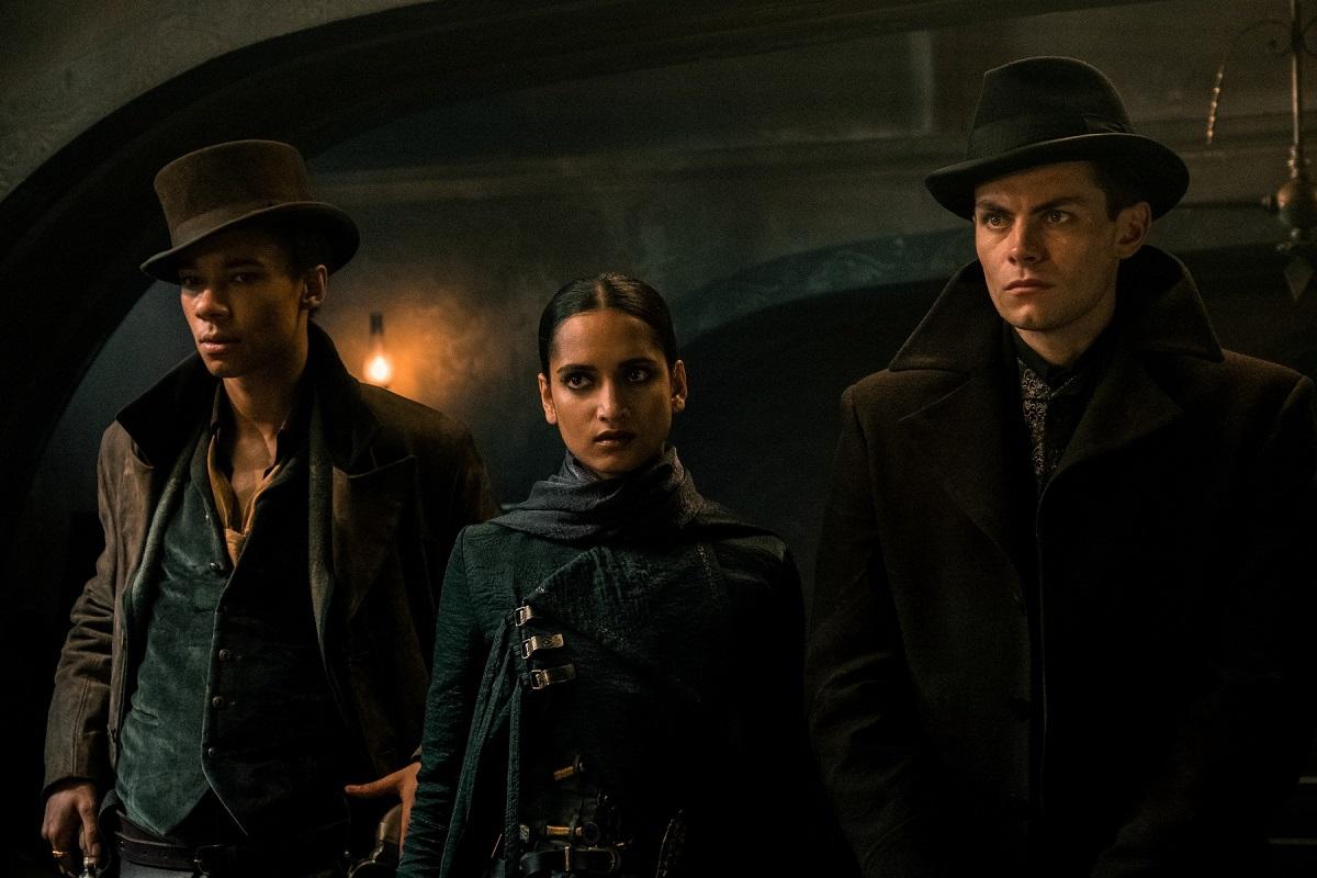 Personajele Malyen Orestev, Inej Ghafa și Kaz Brekker interpretate de acotrii Archie Renaux, Amita Suman și Freddy Carter intrand într-o încăpere într-una din scenele serialului Shadow and Bone