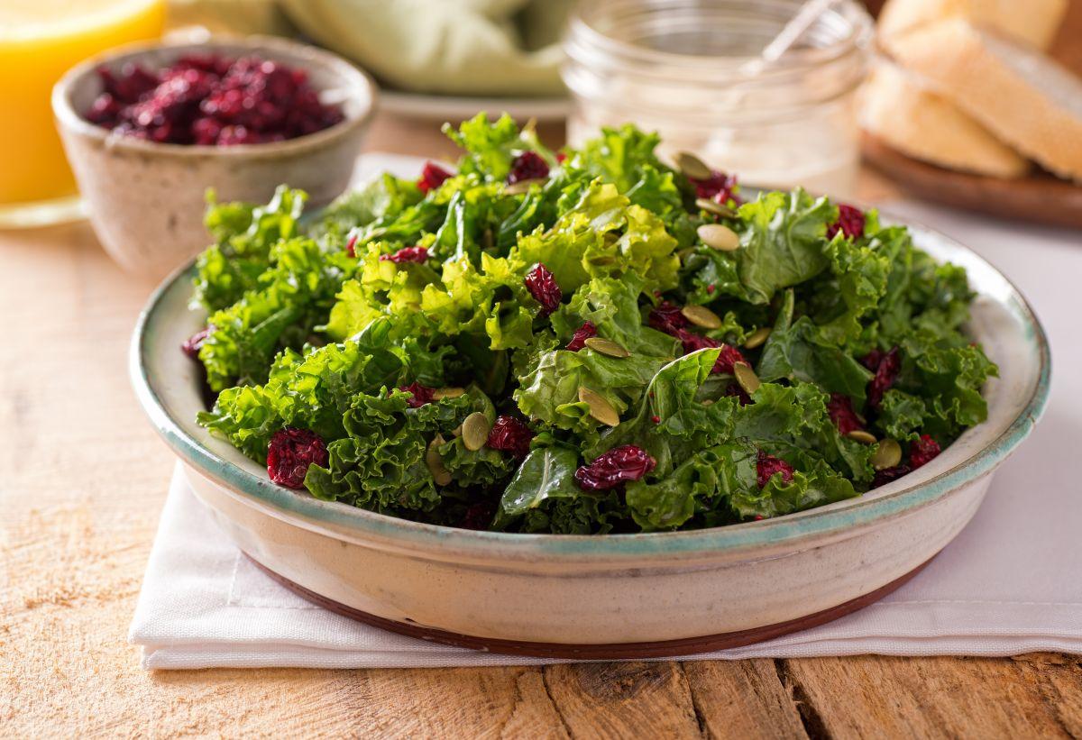 O salată de kale cu merișoare și oleaginoase, într-un bol, așezat pe o masă