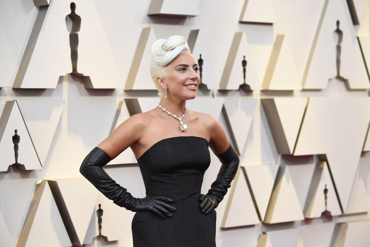 Lady Gaga poartă o rochie neagră de satin, fără umeri, și mănuți lungi. Aceasta participă la cea de-a 91- ediție a Premiilro Oscar