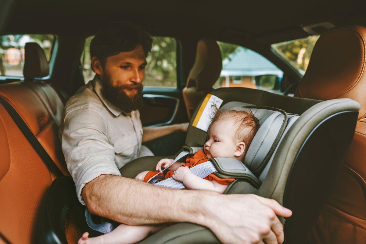 Un tată își aranjează bebeușul în scaunul rear-facing