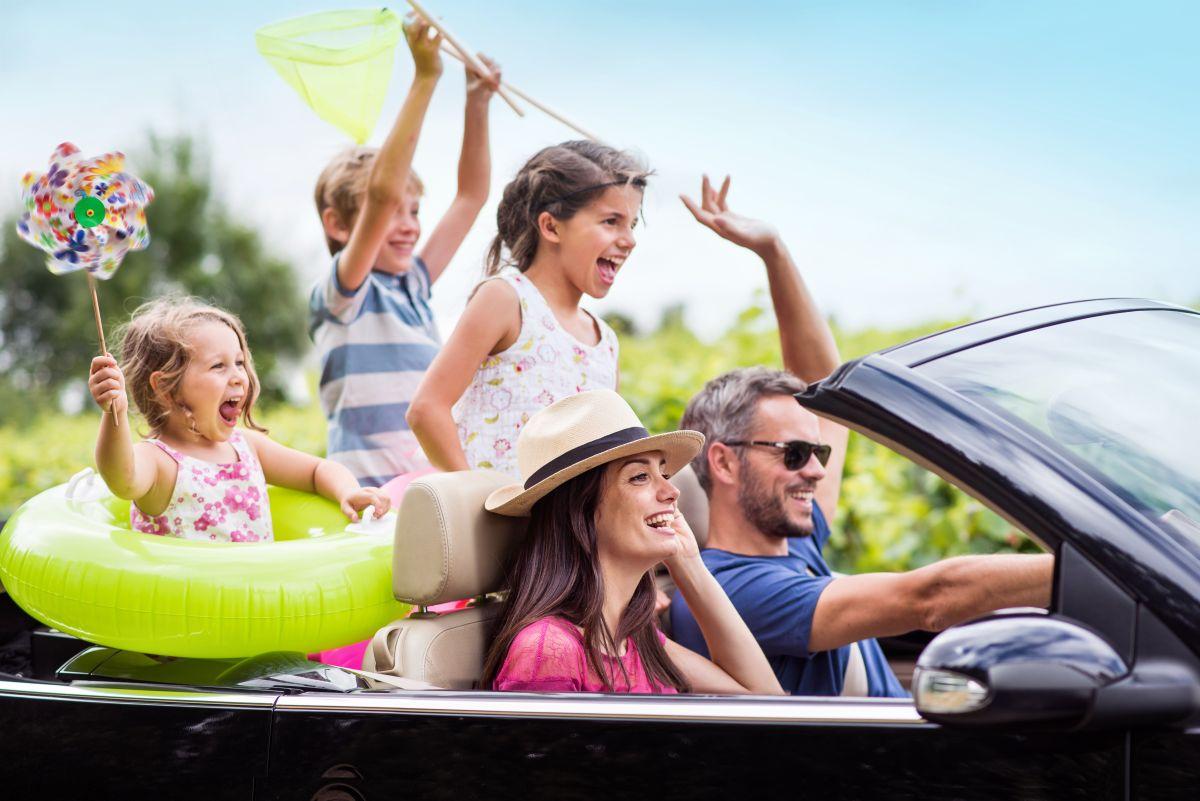 Un cuplu călătorește întro mașină decapotabilă, alături de cei trei copii