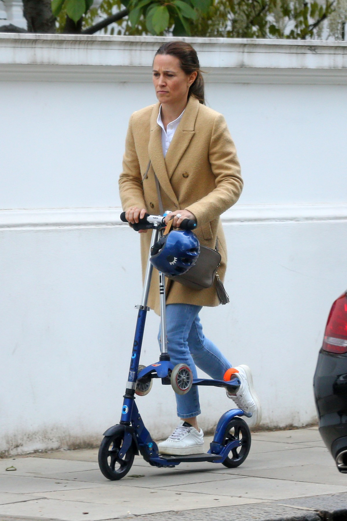 Pippa Middleton pe trotinetă îmbrăcată într-un palton crem, în timp ce ține în mână trotineta și casca de protecție pentru băiețelul său Arthur