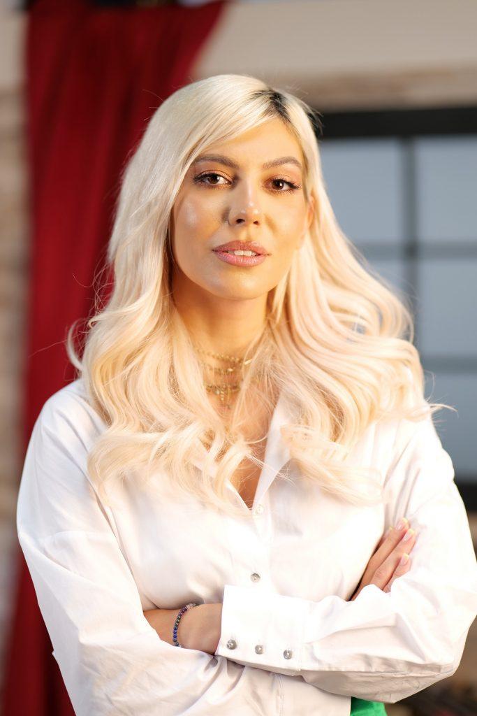Sore în prim plan în timp ce zâmbește la cameră și își ține mâinile încrucișate, î,brăcată într-o cămașă albă și cu părul desfăcut pe umeri