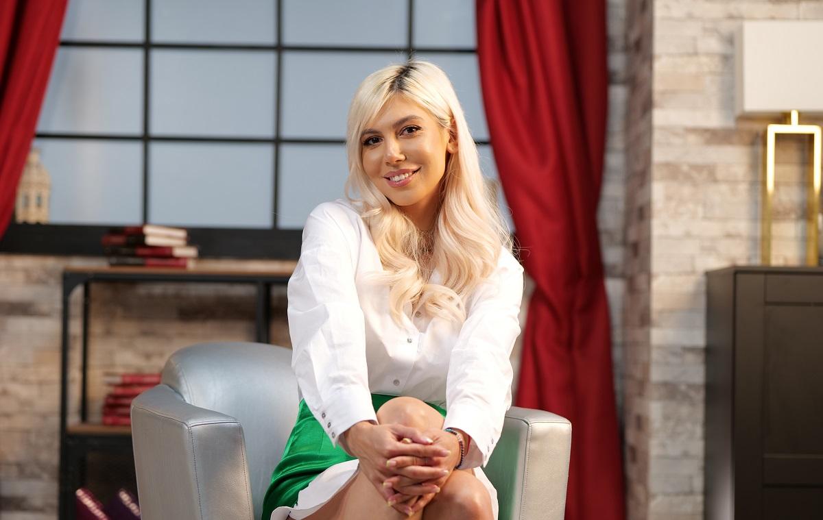 Sore înbrăcată într-o cămașă albă și o fustă verde în timp ce stă jos cu un picior peste celălalt și zâmbește la cameră