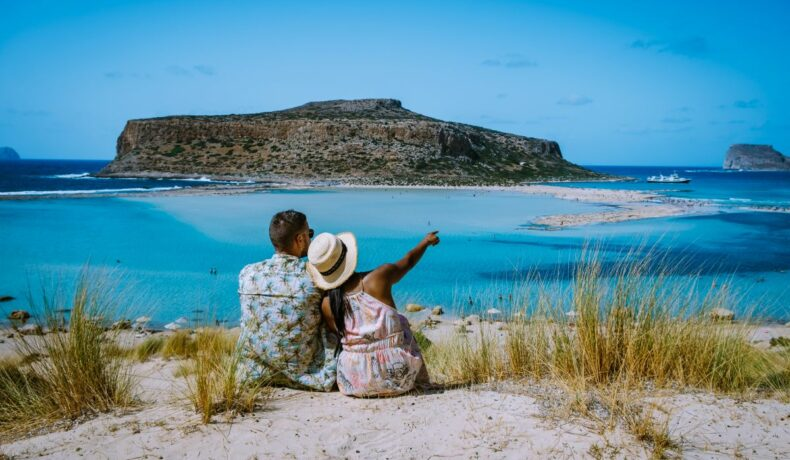 Un cuplu ce stă pe plajă și amiră peisajul, în Creta, Grecia