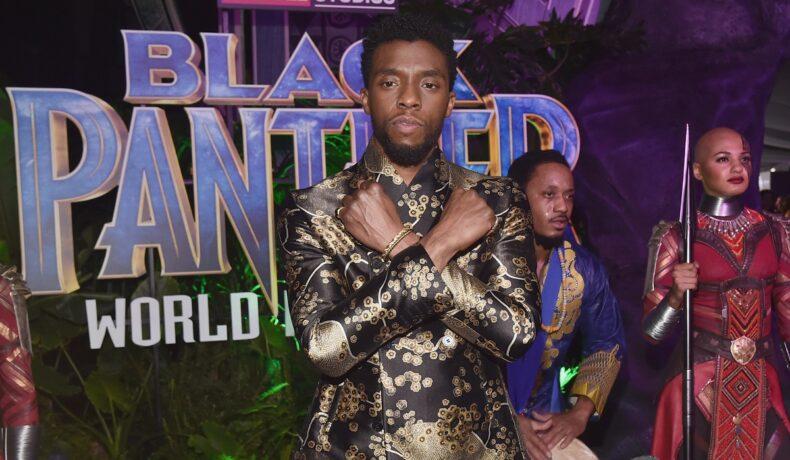 actorul Chadwick Boseman îmbrăcat într-un costum argintiu ținând mâinile încrucișate la premiera filmului Pantera Neagră