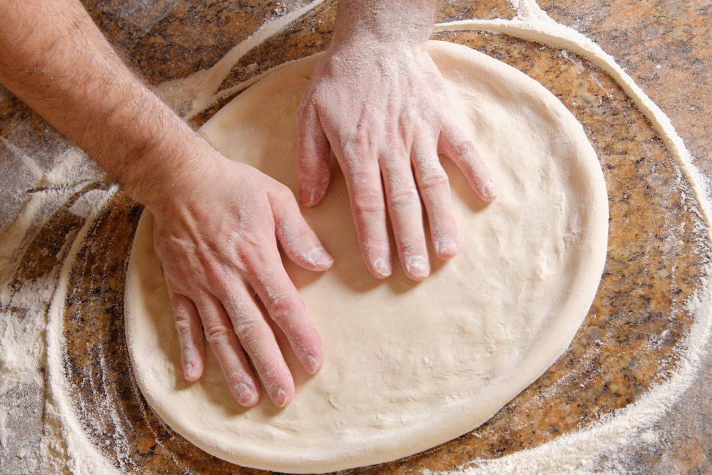 Aluat de pizza întins pe un blat de lemn