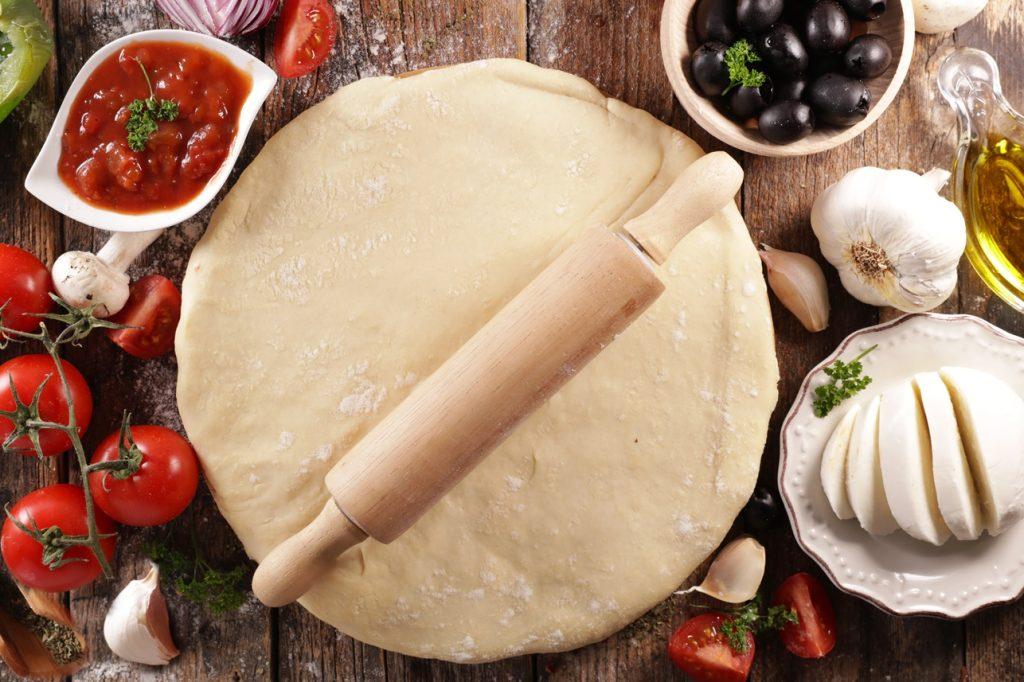 Aluat de pizza întins cu sucitorul de aluaturi, alături de ingrediente pentru topping