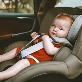 Un bebelul, îmbrăcat în arămiu, este așezat într-un scaun rear-facing