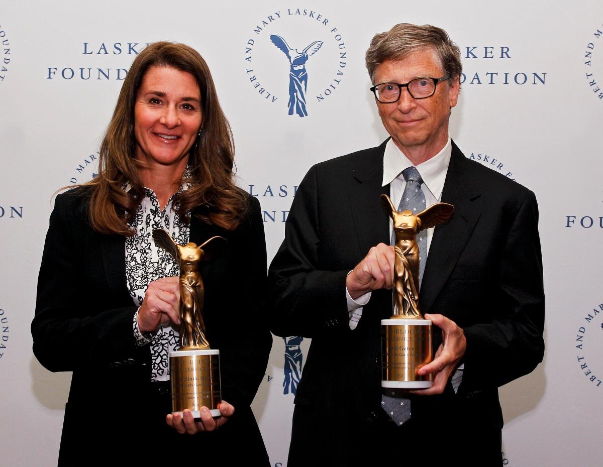 Bill Gates alături de soția lui. Ambii țin în mână câte un trofeu câștigat pentru activitatea lor filantropică.