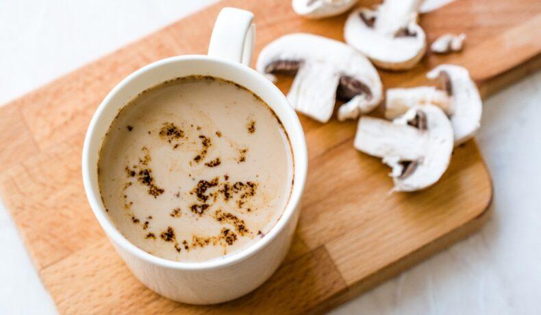 O cana de cafea cu ganoderma și niște ciuperci pe un tocător