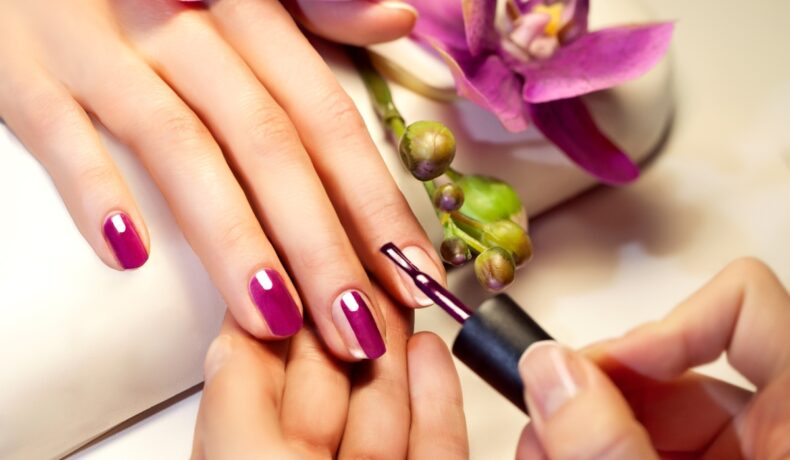 O femeie îi vopsește unghiile altei femei cu o ojă de culoare mov