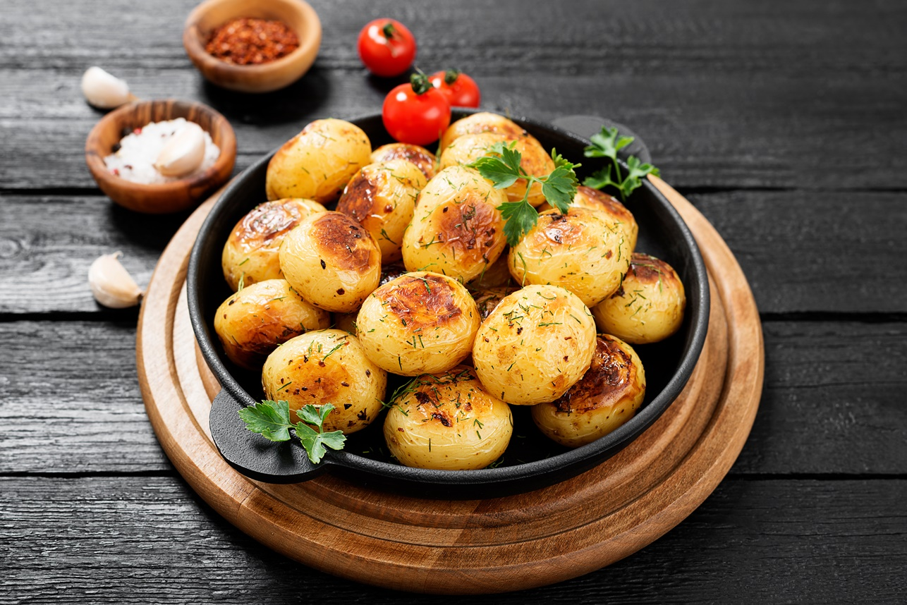 Cartofi noi preparați la cuptor, într-o formă termorezistentă, pe un blat de lemn