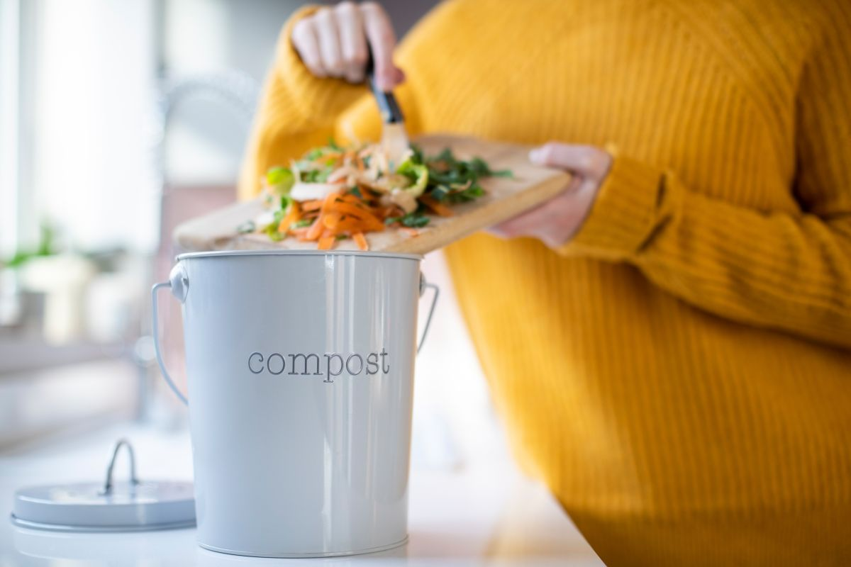 Mâinile unei femei care aruncă resturile de legume de pe un tocător, într-o găleată de compost