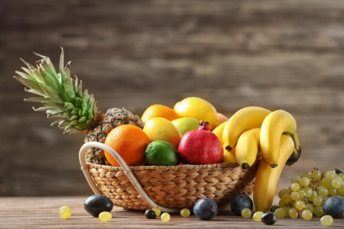 Un coș cu mai multe fructe: ananas, banane, avocado, citrice.
