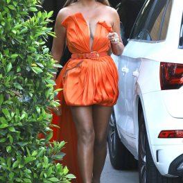 Chrissy Teigen, în timp ce iese din casă, cu o rochie portocalie cu trenă