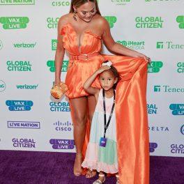 Chrissy Teigen și Luna, la panoul media, în timp ce micuța stă ascunsă sub trena rochiei