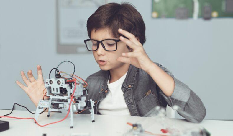Un băiat construiește un robot, în timp ce are o cămașă gri și ochelari și stă la o masă, iar în fața sa se află roboțelul