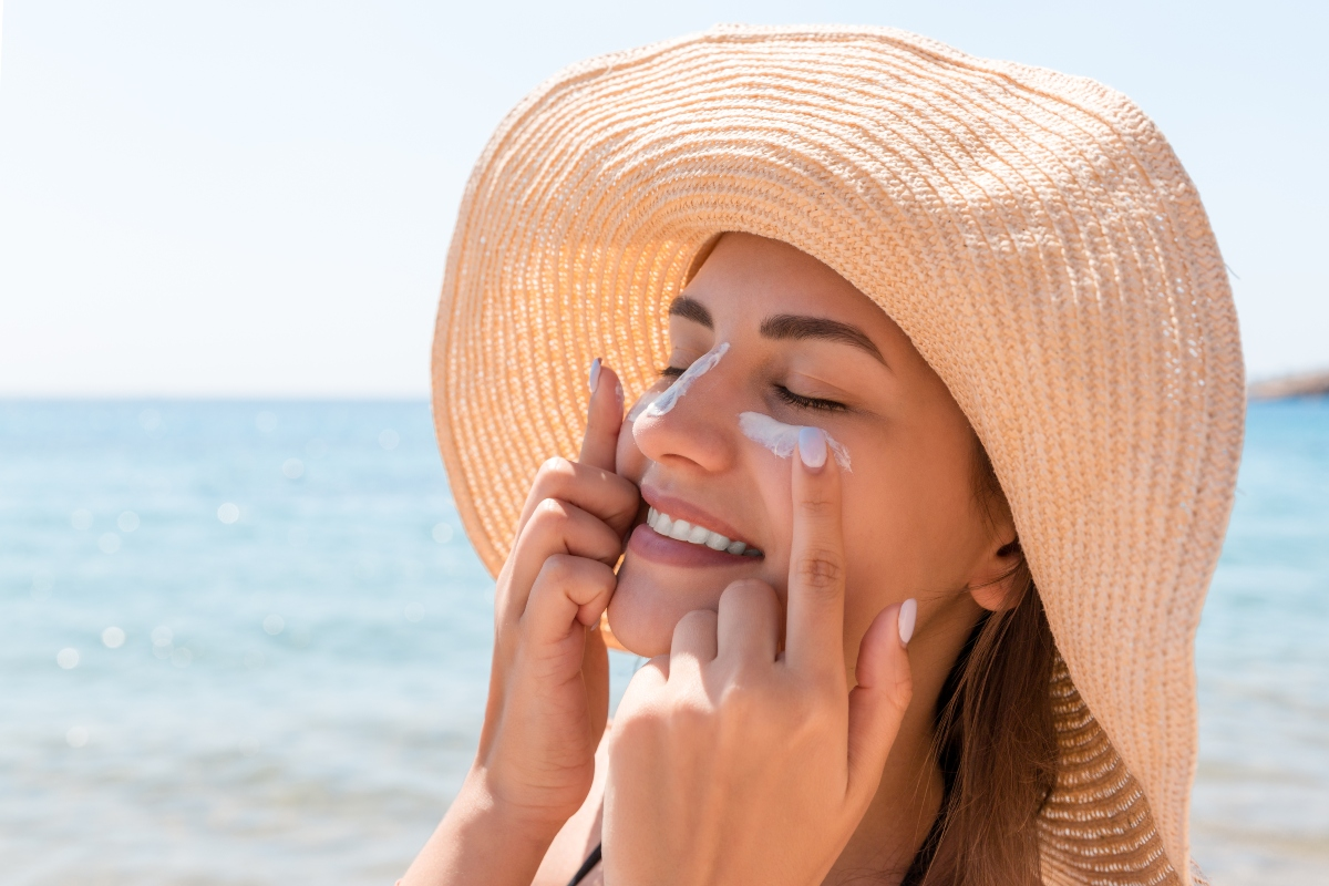 O femeie cu pălărie bej, cu boruri mari își aplică o cremă cu protecție solară pe față