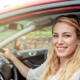 O femeie la volanul unei mașini.