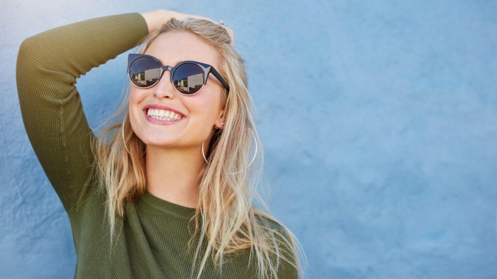 O femeie în bluză verde, cu ochelari de soare negri, zâmbește