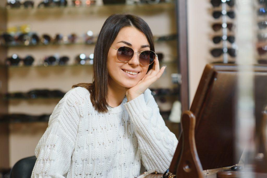 O femeie cu ochelari de soare la ochi privește un ecran.