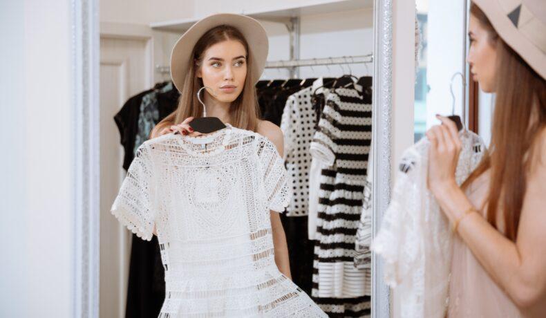 O femeie măsoară o rochie albă în fața oglinzii.