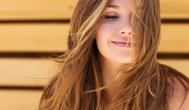 O femeie cu păr lung zâmbește.