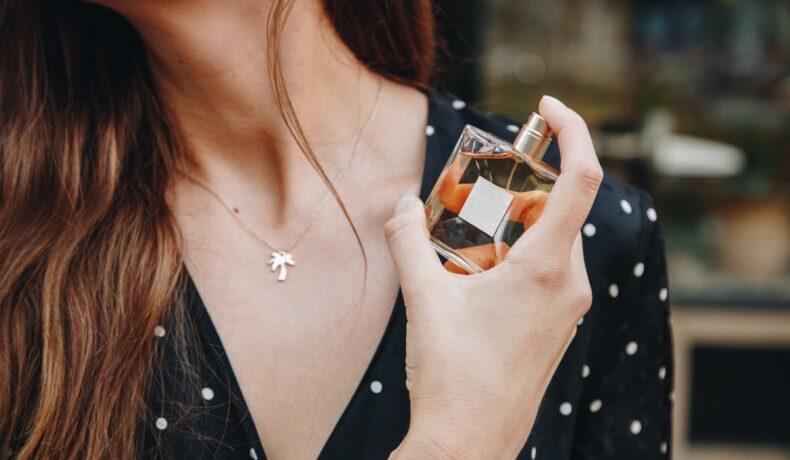 O femeie în bluză neagră cu buline albe, își pulverizează parfum pe pielea gâtului.