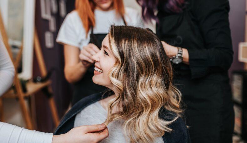O femeie blondă este la salon este coafată de trei hair styliști.