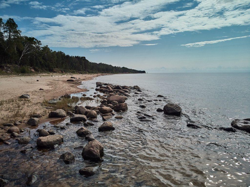 plajă acoperită cu stânci și apă cu un cer albastru și senin într-o imagine care denotă vacanța de vis