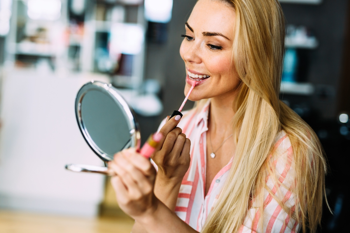 O femeie blondă, ține o oglindă rotundă în mână și își aplică un ruj pe buze