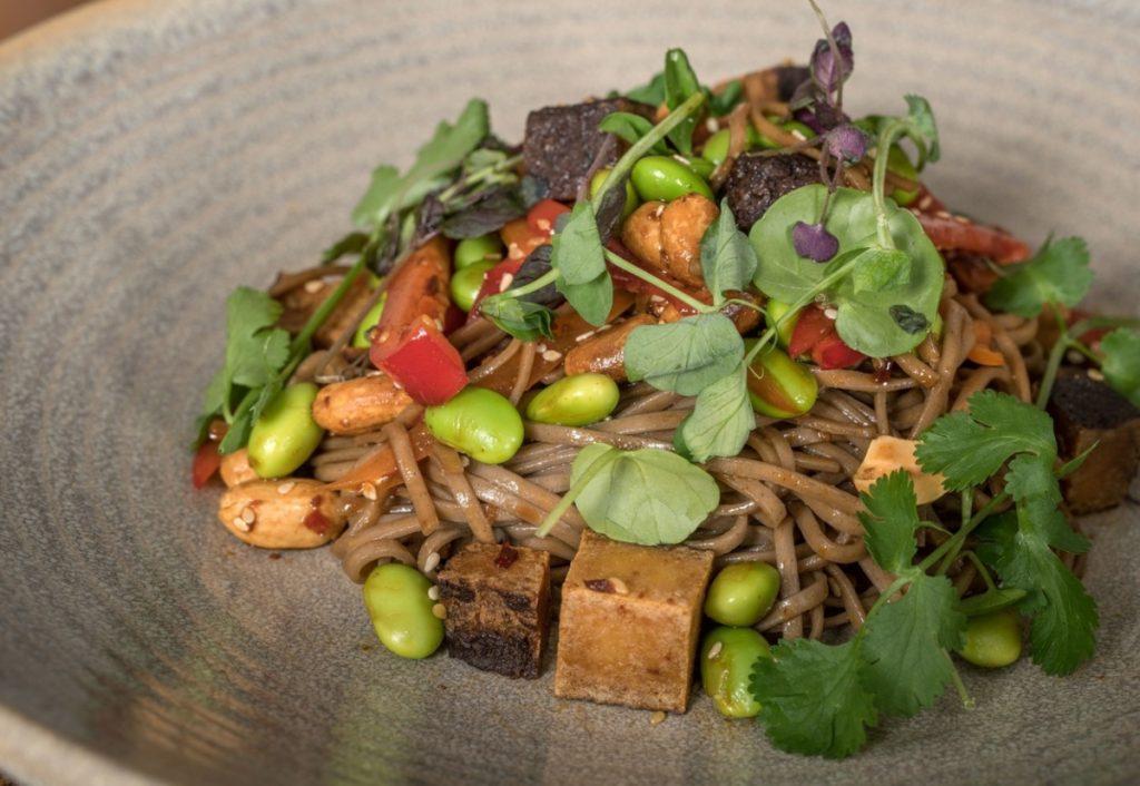 Tofu afumat într-o farfurie cu salată verde, noodle și nuci,