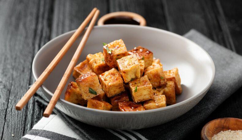Într-un bol alb sunt cuburi de tofu prăjit. Pe farfurie sunt niște bețișoare pentru servit.