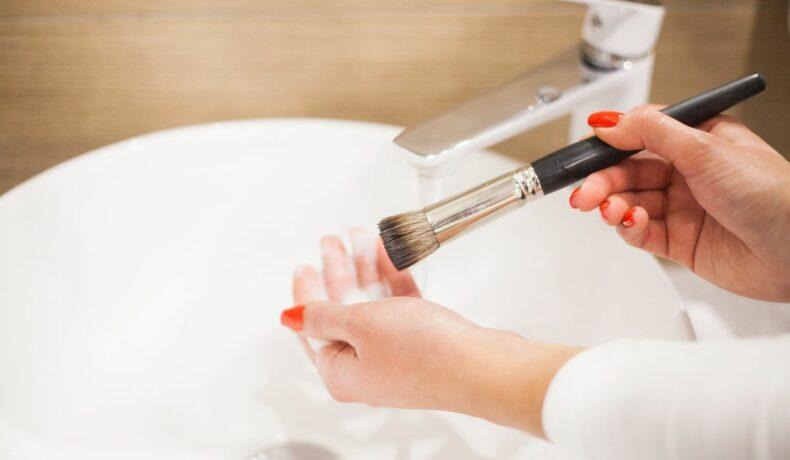 O femeie curăța o pensulă de machiaj sub jetul de apă al unei chiuvete.