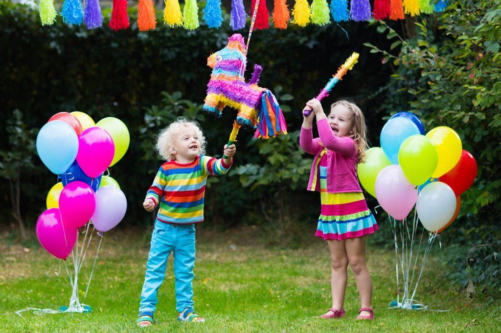 O fetiță și un băiețel într-o grădină îmbrăcați foarte colorat în timp ce încearcă să lovească o Pinata colorată în formă de căluț într-una din acele activități creative de 1 iunie