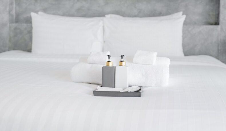 un pat cu așternuturi albe pe care sunt așezate două sticluțe de culori alb și gri, alături de prosoape albe pentru a demonstra de ce sunt folosite așternuturile albe în camerele de hotel