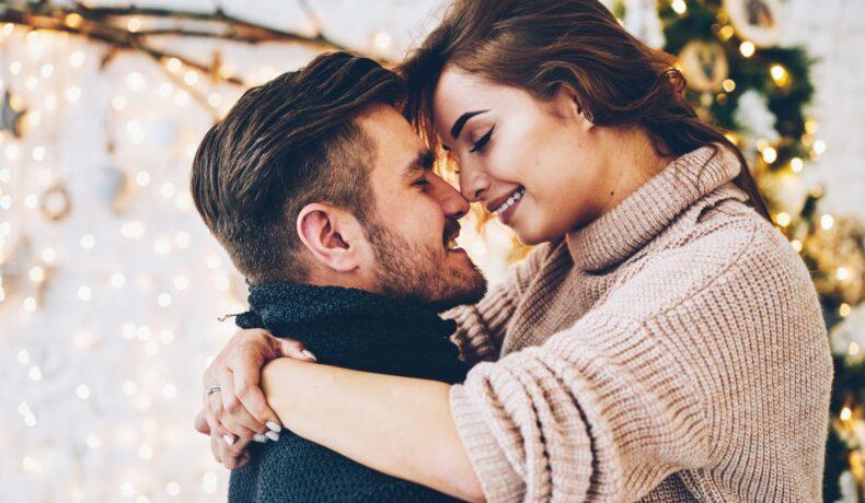 Un cuplu de îndrăgostiți se îmbrățișează. El poartă un pulover negru, ea un pulover bej.
