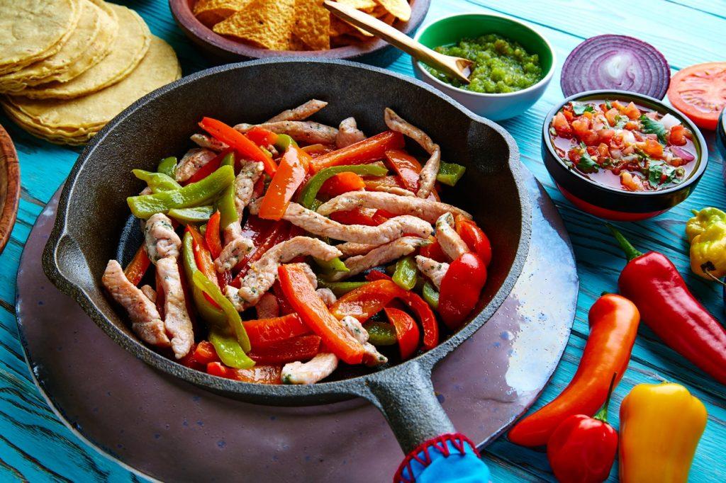 Piept de pui cu ardei șa tigaie pentru fajitas, alături de boluri cu diverse sosuri