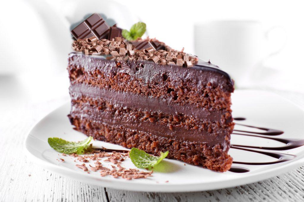 Porție de tort cu ciocolată, decorat cu mentă și bucăți de ciocolată