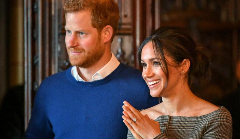 Meghan Markle și Prințul Harry, într-o vizită la Castelul Cardiff, în anul 2018, fotografiați în timp ce zâmbesc la presă
